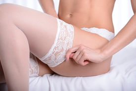 stock photo of panty-hose  - Beautiful sexy woman putting on white stockings in bed - JPG