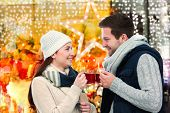 stock photo of hot couple  - Romantic young couple drinking hot wine punch claret on christmas market - JPG