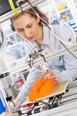 Постер, плакат: girl student makes the item on the 3D printer