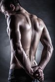 pic of arm muscle  - Strong athletic man back on dark background - JPG