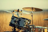 stock photo of drum-set  - Drum set in an open field with warm colors - JPG