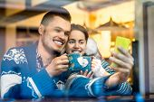 foto of iroquois  - Young loving couple dressed in blue sweater sitting with knitted coffee cups and making selfie photo at the cafe in winter - JPG