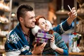image of iroquois  - Young couple making selfie photo with gift boxes at the cafe in winter - JPG
