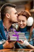 image of iroquois  - Young couple dressed in blue knitted sweaters with gift boxes at the cafe in winter - JPG