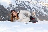stock photo of hurt  - Skier woman hurt lying in the snow of a high mountain - JPG