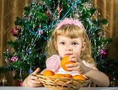 image of tangerine-tree  - Girl with tangerines against New Year tree - JPG