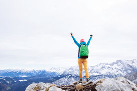pic of climb up  - Female hiker with backpack raised her hands celebrating successful climb to top of mountain - JPG
