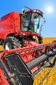 foto of combine  - combine harvester on a wheat field with a blue sky - JPG