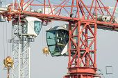 picture of heavy equipment operator  - White and Red Tower Crane Operator Cabins Facing in front of Blue Sky - JPG