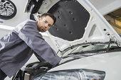 picture of car repair shop  - Portrait of confident male repair worker repairing car engine in repair shop - JPG
