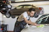 picture of car repair shop  - Young male mechanic cleaning car in repair shop - JPG