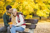 picture of shy woman  - Loving young man hugging shy woman on park bench during autumn - JPG