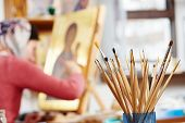 Iconography. brushes heap with woman painting the Mother of God icon on background poster