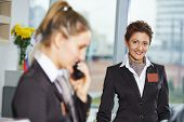 picture of receptionist  - female receptionist workers standing at hotel counter - JPG