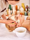 foto of beauty parlour  - Beautician and woman  with clay facial mask in beauty spa - JPG