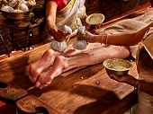 stock photo of ayurveda  - Young woman having feet Ayurveda India spa massage - JPG