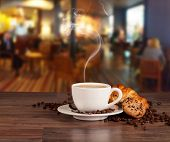 stock photo of croissant  - Coffee drink served with croissant on wooden table with blur cafeteria as background - JPG