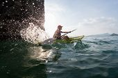 picture of kayak  - Young lady paddling hard the sea kayak with lots of splashes - JPG