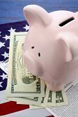 picture of income tax  - USA Tax Day concept with income tax form and cash on stars and stripes flag with piggy bank - JPG