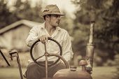 image of farmer  - Young Farmer Driving a Red Old Vintage Tractor - JPG