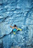 foto of climbing wall  - female rock climber climbs on a rocky wall - JPG