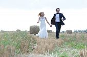stock photo of hay bale  - Married couple running in a hay bale field holding hands and smiling - JPG