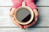 picture of hot-weather  - Female hands holding cup of coffee on wooden background - JPG