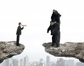 picture of yell  - Businessman using megaphone yelling at black bear on cliff with cityscape background - JPG