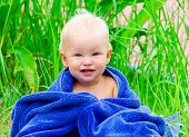 image of naked children  - Little child sitting on the grass with blue towel - JPG