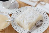 image of condensation  - Rice pudding with coconut on white plate with cup of coffee and condensed milk on table - JPG
