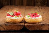 picture of scallion  - Two sandwiches with cured salmon cream cheese parsley capers and scallion on old wooden boards with space - JPG