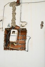 stock photo of electricity meter  - Unfinished wiring and electricity meter on a wall - JPG