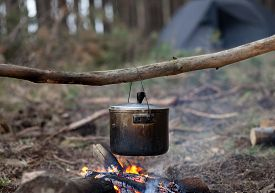 foto of smut  - Cooking in sooty cauldron on campfire at forest - JPG