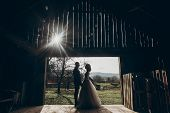 Stylish Bride And Groom Hugging In Sun Light On Background Of Wooden Wall In Barn. Rustic Wedding Co poster