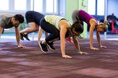 fitness, sport and healthy lifestyle concept - group of people exercising in gym poster