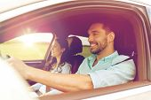 leisure, road trip, travel, family and people concept - happy man and woman driving in car poster