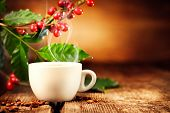 Coffee. Cup of steaming coffee with the real coffee ripe berries, flowers and leaves on a branch of  poster