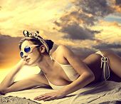 stock photo of sun-tanned  - Beautiful woman lying on the sand and tanning - JPG