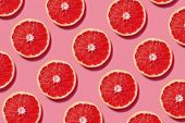 Colorful fruit pattern of fresh grapefruit slices on pink background. Minimal flat lay concept. poster