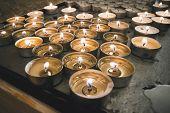 Burning Memorial Candles On The Dark Background. Many Round Memorial Candles In The Candlesticks. Bu poster