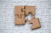 4 Four Brown Pieces Of Puzzle On A White Jigsaw Background, Last Piece Of Jigsaw Puzzle To Complete  poster