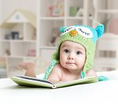 Baby In Funny Owl Knitted Hat Owl Lying With Book In Nursery poster