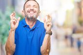 Middle age hoary senior man over isolated background smiling crossing fingers with hope and eyes clo poster