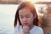 Multicultural Little Girl Praying With Sunflare Background poster