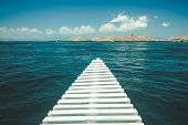 Close-up white pier leading to the ocean. Komodo island, Indonesia. Amazing marine scene. The cloudy poster
