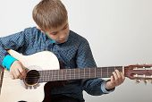 pic of 13 year old  - 13 year old teenage boy concentrating on playing acoustic guitar - JPG