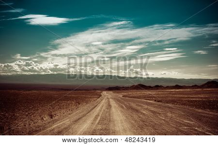 Empty Rural Road Going Through Prairie Under Cloudy Sky In Charyn Canyon poster