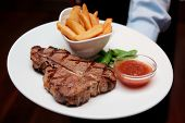 Waiter offering T-bone steak with french fries and hot sauce