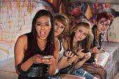 stock photo of insults  - Insulted pretty young woman with friends on phones - JPG