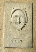 foto of andong  - korean mask of a female face carved in stone in seoul south korea - JPG